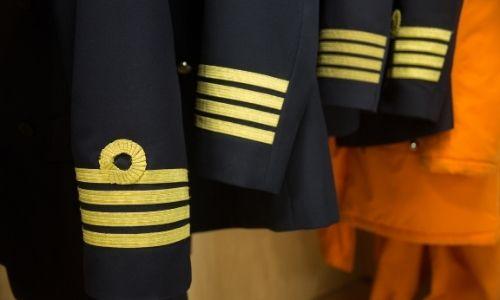 4 uniformes bleu marine d'un équipage rangés dans une armoire, vu sur les manches et les distinctions (bandes dorées et boucle)