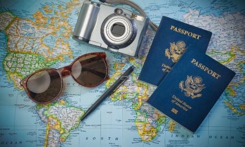 Carte du monde sur laquelle se trouvent un appareil photo, 2 passeports, une paire de lunettes de soleil et un stylo
