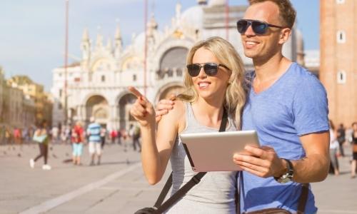 Un couple visitant eux-mêmes une ville à l'aide d'une tablette