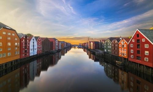 Trondheim au coucher du soleil avec petites maisons en bois de couleurs rouge, jaune moutarde, blanche et marron, avec rivière au milieu