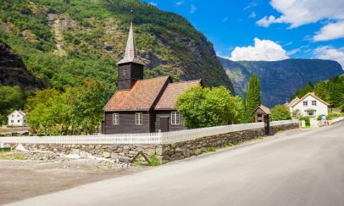 L'église de bois de Flam, en bois de couleur foncée, en plein milieu de la nature, bord d'une route