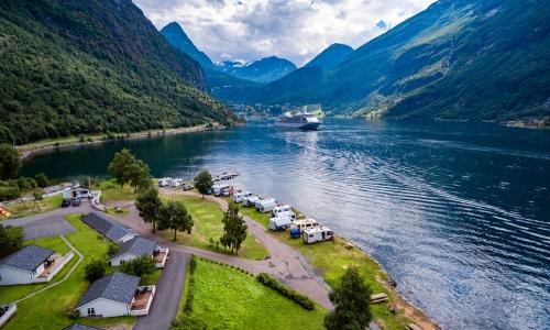 Vue sur le paysage des fjords avec mer calme, habitations, verdure et bateau de croisière au loin