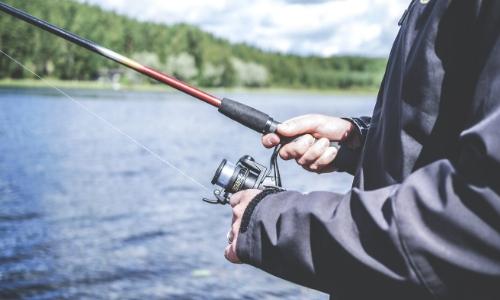 Gros plan sur une personne représentée par ses mains tenant une ligne de pêche avec paysage maritime en arrière plan