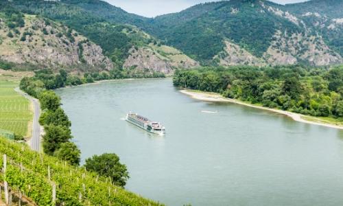 Vue en hauteur sur le fleuve du Danube, avec bateau naviguant, entouré de verdure