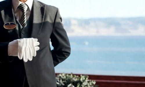 membre d'un équipage d'une croisière en costume portant un gant sur sa main et l'autre dans sa main, la photo ne présente que le buste de l'homme