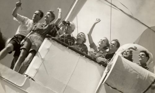 photo en noir et blanc d'un groupe de personnes qui sont à bord d'un bateau, et disent au-revoir d'un signe de la main, avec enthousiasme
