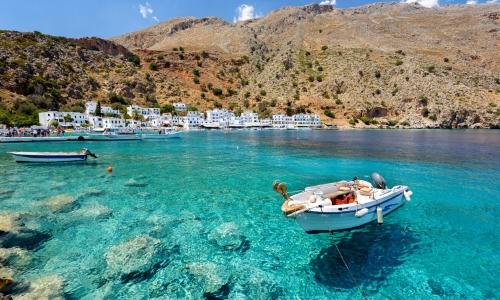 Vue sur la Crète, eau transparente, collines, petites habitations blanches, petites barques sur l'eau
