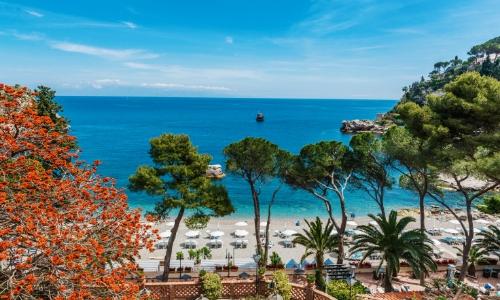 Vue en arrivant sur la plage à Taormine, avec arbres, transats, parasols
