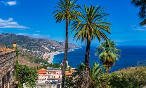 Vue sur la mer depuis Taormine avec palmiers, habitations et montagnes