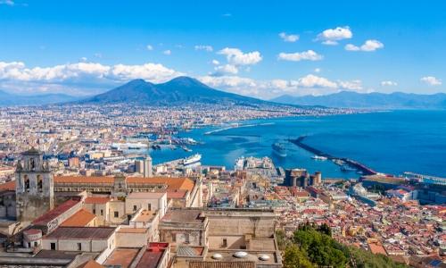 Vue sur le port de Naples, avec des habitations et le Vésuve au loin