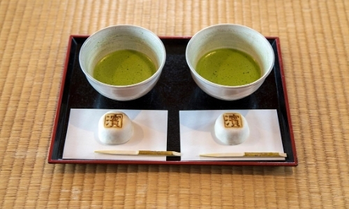 Deux bols de thé vert matcha accompagnés d'une petite friandise