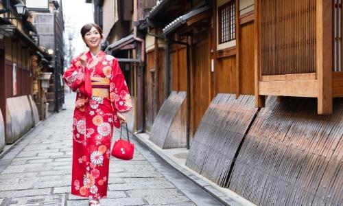 Femme souriante marchant dans la rue en kimono