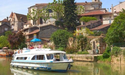 bateau sur un canal qui long un petit village