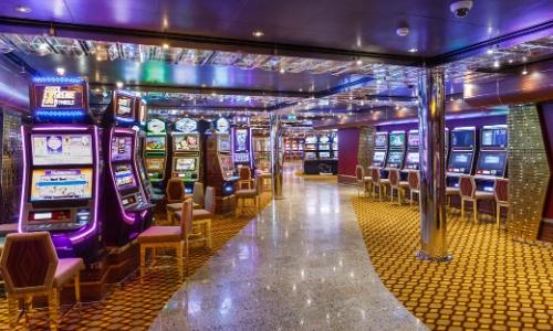 Intérieur d'un casino dans un bateau de croisière, avec machines à sous, chaises...