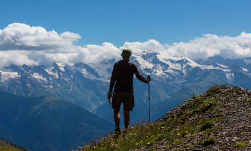 Homme de dos, au sommet d'une montagne, montagnes enneigées au loin