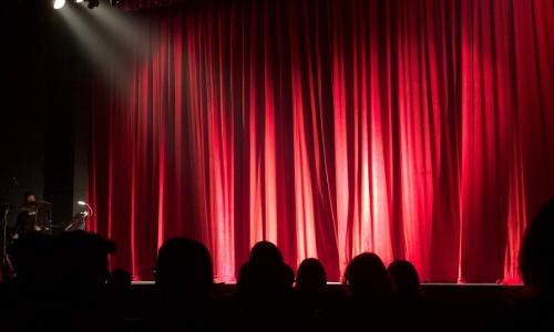 Dans une salle de spectacle, vue sur une scène avec rideau rouge, projecteurs