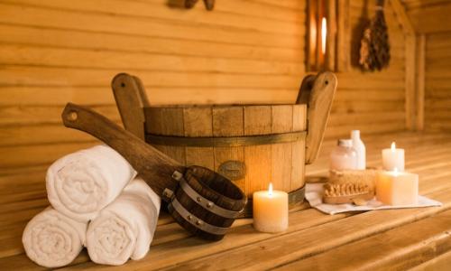 Intérieur sauna avec serviettes, bougies, pierres chaudes dans un bol