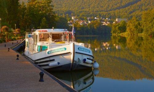 bateau sans permis à quai, à l'aube sur une rivière en Ardennes