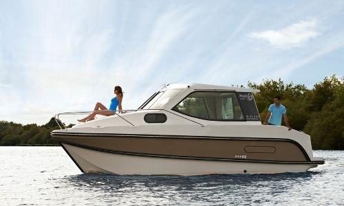 bateau sans permis nicols 1 cabine, sur l'eau, un couple profitant du soleil