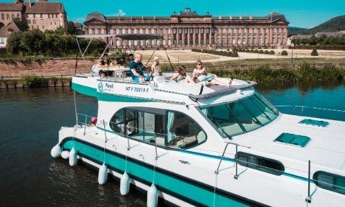 bateau sans permis à 4 cabines sur un fleuve, avec à son bord des vacanciers sur le toit