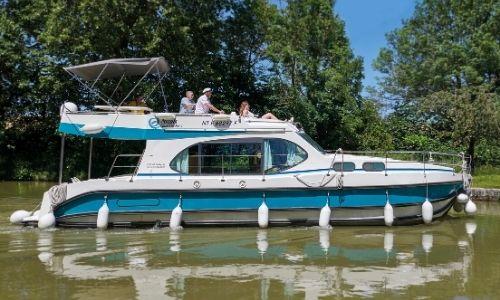 bateau Nicols sur l'eau, occupé par des vacanciers sur un canal