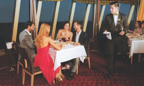 Groupe de personnes mangeant en s'amusant dans un restaurant du navire avec plat, verre de vin et serveur à côté