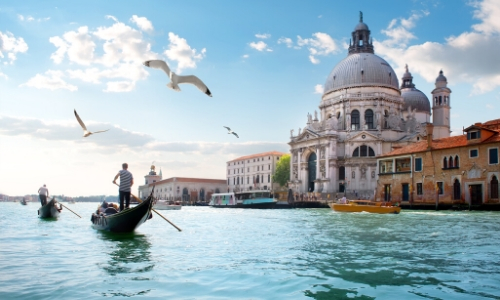 Photo de Venise en Italie avec gondoliers naviguant, ainsi que des habitations et monuments