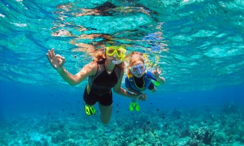Une femme et son enfant sous l'eau pratiquant le snorkelling