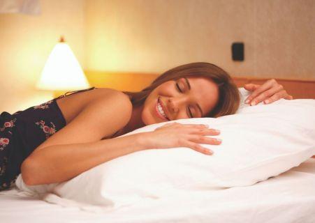 jeune femme allongée sur le lit dans une cabine de croisière, la tête sur l'oreiller avec le sourire aux lèvres