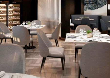 intérieur d'un restaurant avec les tables dressées dans une ambiance taupe, neutre et épurée prêt à accueillir les convives.