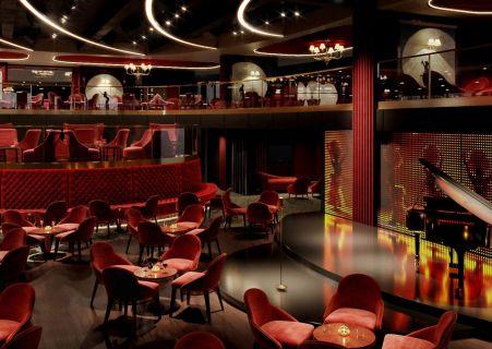 salle de spectacle ambiance cabaret, lumières tamisées, fauteuils et tables rouges avec une scène qui dispose d'un piano et d'un rideau lumineux en fond.