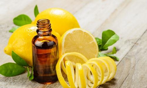 Flacon d'huile essentielle avec rondelles de citrons autour, et citrons entier, zestes