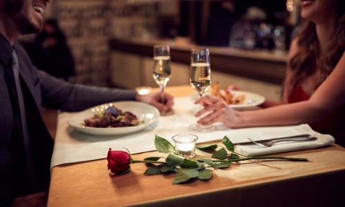Couple autour d'une table, verre de vin à la main, plats sur la table