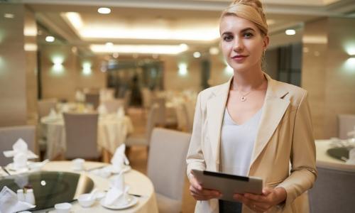 Portrait d'une wedding planner, sur fond de tables préparées pour une soirée/cérémonie