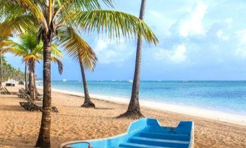 Palmiers des Caraïbes sur une plage avec un bateau bleu sur le sable