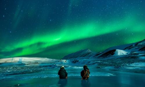 Vue sur 2 personnes assises, admirant les aurores boréales