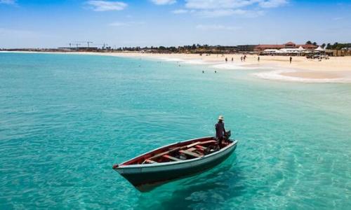 Eaux limpides du Cap-Vert, avec barque sur l'eau et plage de sable blanc