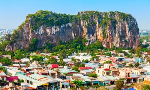 Petites habitations au pieds des montagnes de marbre avec beaucoup de verdure au Vietnam