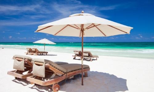 Transats et parasols blancs sur une plage de sable blanc au Caraïbes