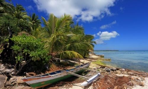 Pirogue traditionnelle sur sable blanc avec palmiers, autres arbres, eau turquoise