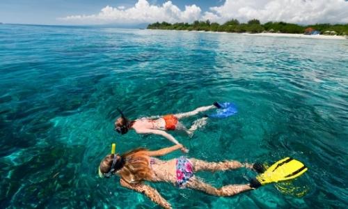 2 personnes entrain de faire du snorkeling dans une eau turquoise