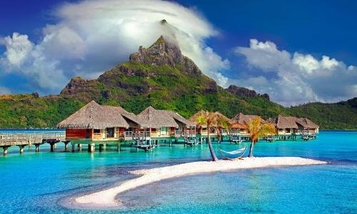 Paysage polynésien avec maisons les pieds dans l'eau, montagne en arrière-plan, sable blanc, eau turquoise