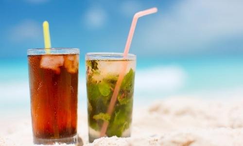 Vue sur 2 cocktails tropicaux sur une plage de sable blanc
