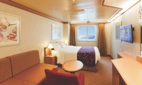 Cabine extérieure avec hublot et vue mer, grand lit, table, canapé, télé