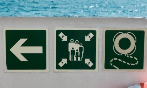 Signalétique sur un bateau de croisière, flèche montrant une direction, pictogramme présentant le point de rassemblement et bouées de sauvetage