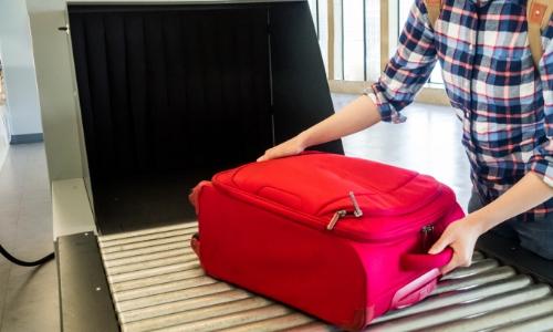 Personne posant sa valise prête à rentrer dans le scanner pour contrôle