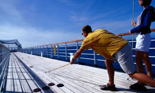 Couple jouant au shuffleboard sur pont d'un bateau