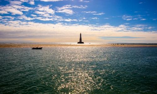 Vue sur l'estuaire de la Gironde avec phare en arrière-plan et un petit bateau naviguant