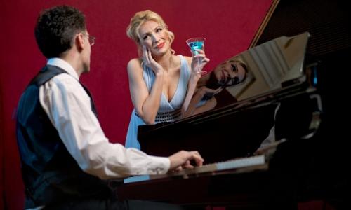 Un homme faisant du piano pendant qu'une femme chante à côté
