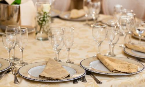 Table aspect chic avec différents verres, assiettes, couverts, serviettes, ambiance dorée